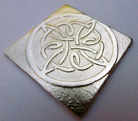 Celtic knotwork design etched on silver